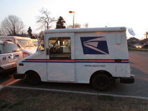 USPS mail delivery truck with logo in Edison, NJ USA. White, blue and red painted mail delivery truck on parking lot Royalty Free Stock Images