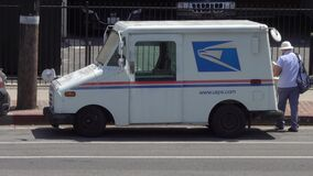 USPS Postal Service Delivery Truck with Mail Carrier Wearing Protective Mask