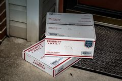 UsPS Priority Mail Boxes. Lancaster, PA, USA - December 15, 2017: USPS Priority Mail boxes packages delivered at a residential home front door royalty free stock images