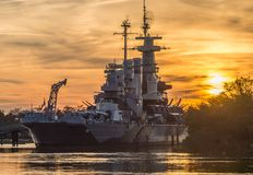 USS North Carolina Battleship. Battleship sets on the cape fear river running high from the hurricane. Sunset in the clouds royalty free stock photo