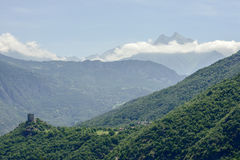 Ussel castle and village with clouds around peak Torche, Italy. Landscape of the valley with Ussel castle and village, in background thin clouds surrounding peak Stock Images