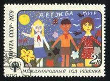 USSR - CIRCA 1979: En stämpel som skrivs ut i USSR, visar barnen som drar kamratskap, circa 1979 Arkivfoto