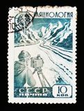 USSR Russia postage stamp shows glaciology researcher with device at glacier in mountain, circa 1959. MOSCOW, RUSSIA - JUNE 26, 2017: A stamp printed in USSR stock photo