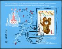 USSR - 1980: visar emblemet av OS:en 1980, Mischa Holding Olympic Torch, avslutning av 22nd sommarOS royaltyfri fotografi