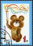 USSR - 1980: visar emblemet av OS:en 1980, Mischa Holding Olympic Torch, avslutning av 22nd sommarOS royaltyfri bild