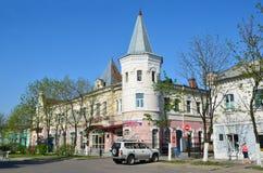 Ussuriysk,俄罗斯, 2016年5月, 19日 在19世纪末的建筑学的纪念碑的附近汽车- tradin的百货商店 免版税库存照片