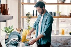 Ust add some milk. Handsome young man in casual wear preparing corn flakes and smiling while standing in the kitchen at home royalty free stock photos
