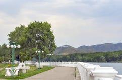 Ust-Kamenogorsk Oskemen in Kazakh, Kazakhstan - July 10, 2017. Irtysh River Embankment, Ablaketka Mountain with KAZAKHSTAN Big. Letters Sign, National Flag and stock photography