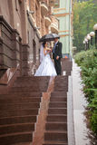 Ust married couple kissing on stairway at rain Royalty Free Stock Photography