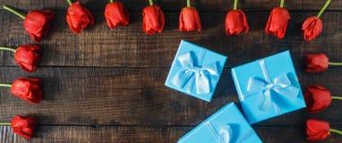 Ustalony błękitny prezenta pudełko z czerwonymi tulipanami na drewnianym tle Zdjęcie Stock
