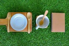Ustawia flatware, pustego talerza i filiżanki na zielonej trawy tle, stylowy wieśniak łyżkę, rozwidla, zdjęcia stock