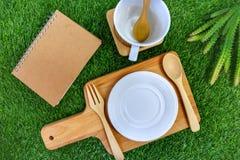 Ustawia flatware, pustego talerza i fili?anki na zielonej trawy tle, stylowy wie?niak ?y?k?, rozwidla, zdjęcia royalty free
