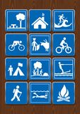 Ustawia ikony schronienie, park, bicykl, bullfight, pikowanie, ognisko, surfing Ikony w błękitnym kolorze na drewnianym tle Fotografia Stock