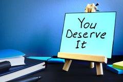 Usted lo merece texto escrito en la tabla Motivación e inspiración imágenes de archivo libres de regalías