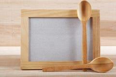 Ustensiles de cuisine et cadre en bois sur un conseil en bois Photographie stock