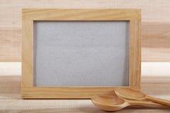 Ustensiles de cuisine et cadre en bois sur un conseil en bois Images stock