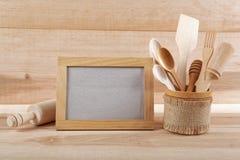 Ustensiles de cuisine et cadre en bois sur un conseil en bois Image stock