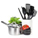 Ustensiles de cuisine, tomate et feuilles en bon état Photographie stock libre de droits