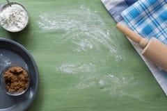 Ustensiles de cuisson, farine, sucre, beurre sur la surface en bois verte Photo libre de droits