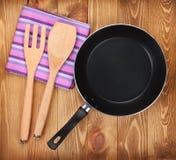 Ustensiles de poêle et de cuisine sur la table en bois Photos stock