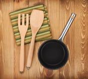Ustensiles de poêle et de cuisine sur la table en bois Photographie stock libre de droits