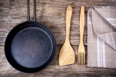 Ustensiles de poêle et de cuisine sur la table en bois Photo stock