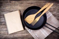 Ustensiles de poêle et de cuisine sur la table en bois Photos libres de droits
