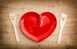 Ustensiles en bois de cuisine et plat rouge de coeur Outils drôles Photos libres de droits