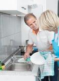 Ustensiles mûrs de nettoyage de couples Photographie stock libre de droits
