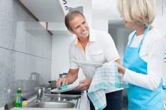 Ustensiles mûrs de nettoyage de couples Photographie stock