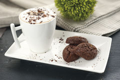 Ustic cookies with cocoa and pistachios on white tray. Ceramic foam cup with cappuccino and cocoa powder, cloth tablecloth and other kitchen items in the Royalty Free Stock Photography