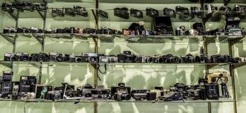 Usty glass shelves full of old film vintage cameras. Badajoz, Spain - October 31, 2017: Dusty glass shelves full of old film vintage cameras over green wall Stock Images