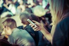 Usuário fêmea do smartphone em público fotografia de stock