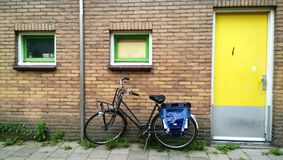 The usual Amsterdam entrance in a residential house, near a parked bike. Bright yellow front door stock photography