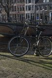 Usual black bike near the canal in the center of Amsterdam. In the sunny autumn day stock image