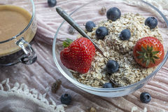 Usual glass bowl with old teaspoon, cereals, strawberries and blueberries, coffee Royalty Free Stock Photo