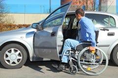 Usuario de silla de ruedas que consigue en un coche Foto de archivo