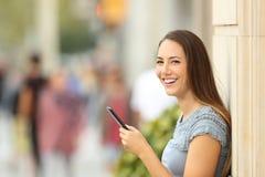 Usuario elegante del teléfono que mira la cámara en la calle Fotos de archivo
