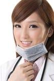 Usura di donna asiatica di medico una maschera chirurgica immagini stock libere da diritti