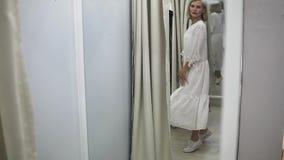 Usura di donna il vestito bianco nel deposito di bagagli Ragazza europea alla moda che guarda nello specchio nella stanza adatta  video d archivio