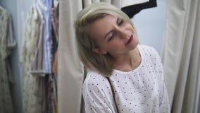 Usura di donna il vestito bianco nel deposito di bagagli Ragazza europea alla moda che guarda nello specchio nella stanza adatta  archivi video