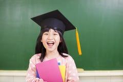 Usura felice della ragazza un cappello di graduazione con la lavagna Fotografie Stock Libere da Diritti