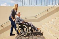 Usuário de cadeira de rodas de ajuda da mulher Fotografia de Stock