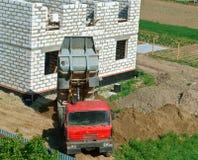 Usyp ciężarówka blisko domowy w budowie budynek dom od białej cegły, ciężarówka, i usyp ciężarówka przynosiliśmy s Fotografia Royalty Free