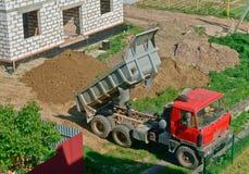 Usyp ciężarówka blisko domowy w budowie budynek dom od białej cegły, ciężarówka, i usyp ciężarówka przynosiliśmy s Zdjęcia Royalty Free