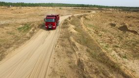 Usyp ciężarówka na otwartej jamy drodze scena Odgórny widok usyp ciężarówki jeżdżenie na glinianym drogowym łupie w wsi z lasem d zbiory wideo
