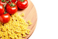 Usypuje farfalle włoskiego makaron i Świeżych Czerwonych dojrzałych pomidory na gre obrazy stock