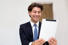 Uszczęśliwionego biznesmena czytelniczy dobre wieści na pastylce Obraz Stock