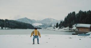 Uszczęśliwiony turystyczny szczęśliwy przyjeżdżający miejsce przeznaczenia w zadziwiającym miejscu z śnieżnym jeziorem wokoło i h zbiory
