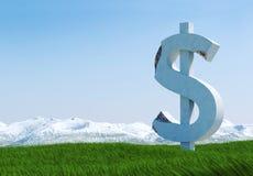 Uszkadzająca betonowa dolarowego znaka statua odizolowywająca na trawy łące z śnieżną górą i niebieskim niebem jako tło Obrazy Stock